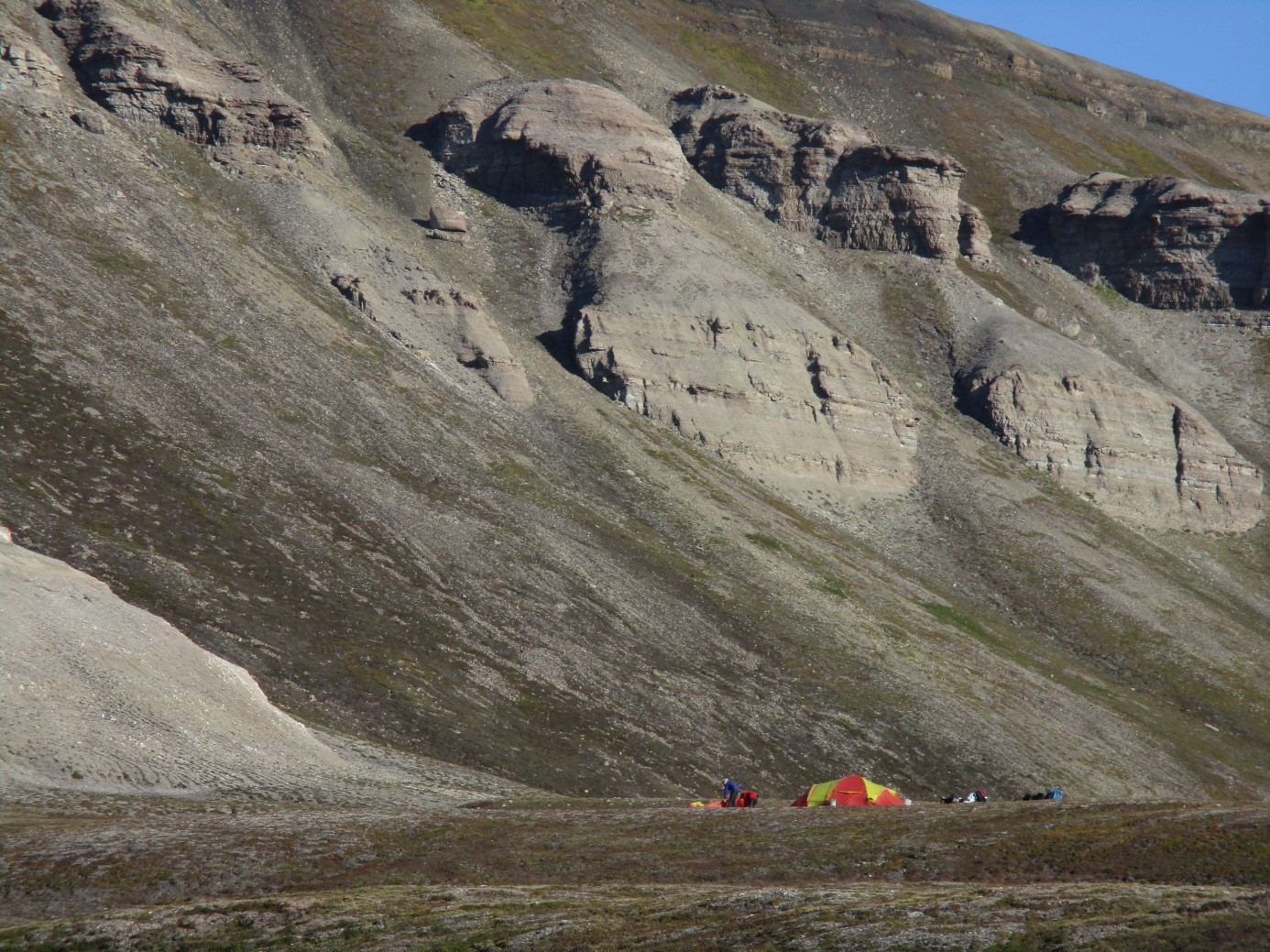 Putting up the tents on a sunny day in the Arctic. In the background you can see the upper parts of the Gipshuken Formation which here consists of dolostones, gypsum and fossiliferous carbonates.