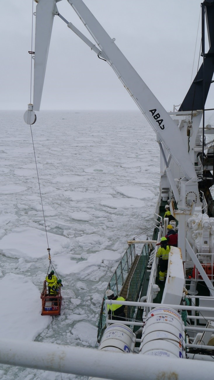 Mar and Philipp using the transporting basket on the crane to get to the ice floe (picture by Ingrid Wiedmann).